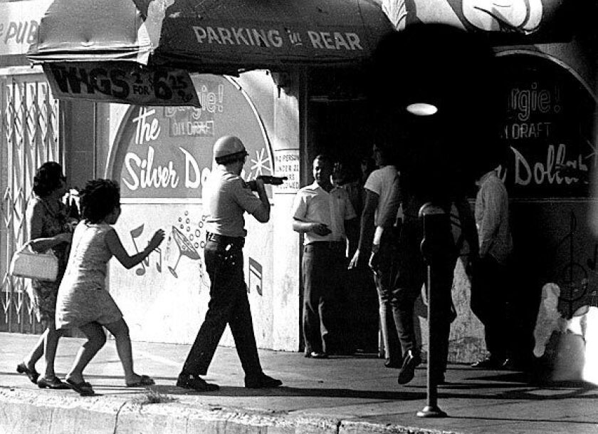 A sheriff's deputy points a shotgun at people outside the Silver Dollar bar, where Los Angeles Times reporter Ruben Salazar was killed on Aug. 29, 1970.