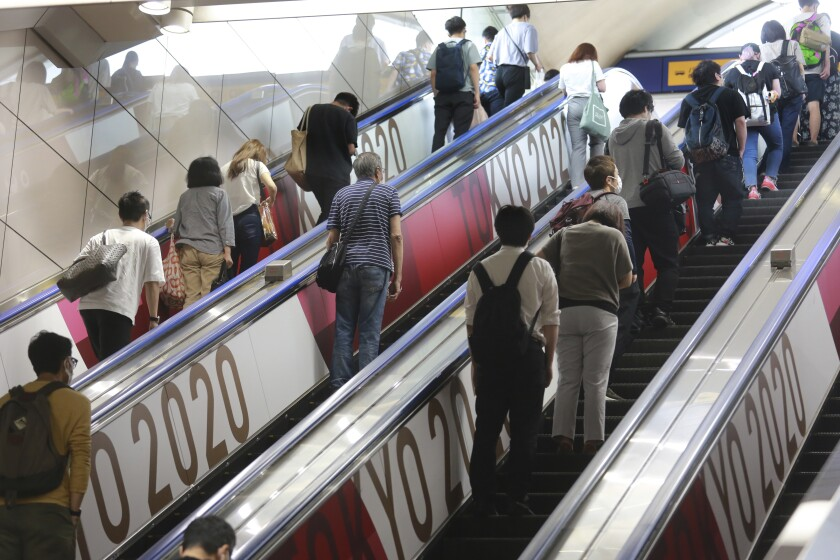People in Tokyo ride escalators with banners July 6 to promote the upcoming Olympics Games.