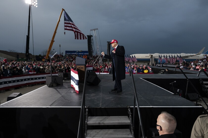Trump pumps his fists on an outdoor stage at a rally in front of Air Force One under cloudy skies
