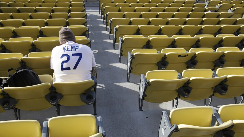A Dodgers fan wearing a Matt Kemp jersey sits in the field level section of Dodger Stadium before a game against the Philadelphia Phillies. The limited availability of Dodgers games on television due to the team's broadcast contract with Time Warner Cable has left many fans frustrated.