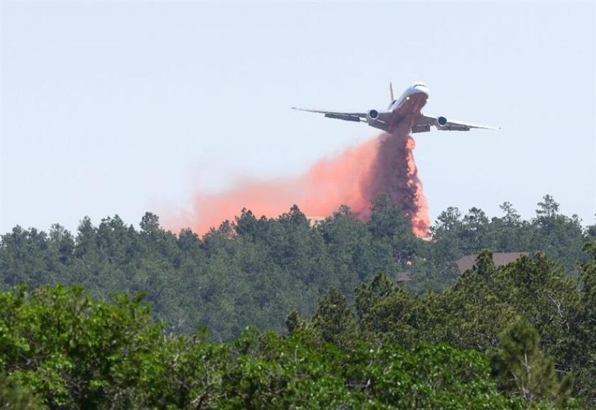 Un avión L911 lanza líquido retardante sobre un incendio en un área de Black Forest, Colorado (EE.UU.). EFE/Archivo