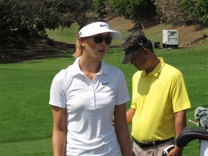 CLARIFIES CAPTION-LPGA golfer Michelle Wie speaks with a spectator while her father, B.J. Wie, looks on during a pro-am ahead of the LPGA Lotte Championship in Kapolei, Hawaii on Tuesday, April 16, 2013. (AP Photo/Oskar Garcia)
