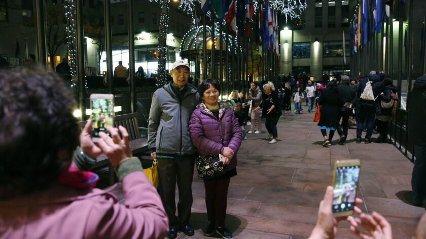 FILE - In this Nov. 12, 2017, file photo tourists from China pose for photographs at Rockefeller Cen