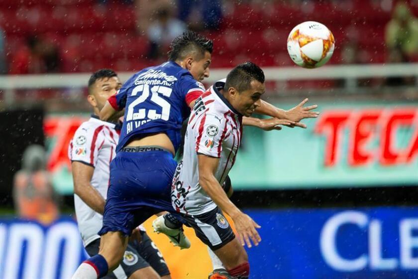 El jugador Edwin Hernández (d) de Chivas disputa el balón con Roberto Alvarado (i) de Cruz Azul durante el partido correspondiente a la jornada 2 del torneo mexicano de fútbol celebrado hoy, sábado 28 de julio de 2018, en el estadio Akron de la ciudad de Guadalajara, Jalisco (México). EFE