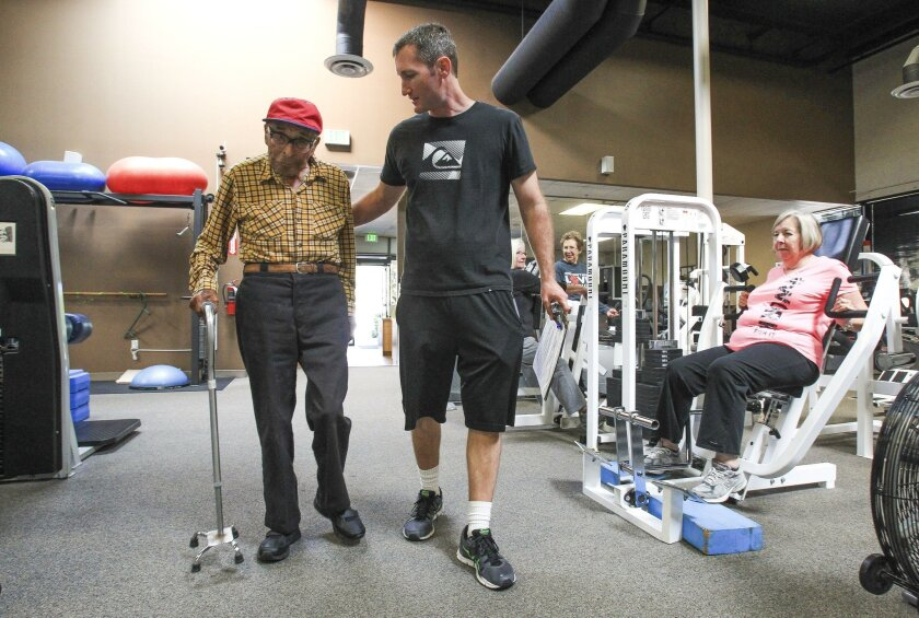 Personal trainer Sean Thompson guides Pearl Harbor survivor Ray Chavez, who will turn 104 on Thursday, to an exercise machine at the Personally Fit Gym in Rancho Bernardo on Tuesday.