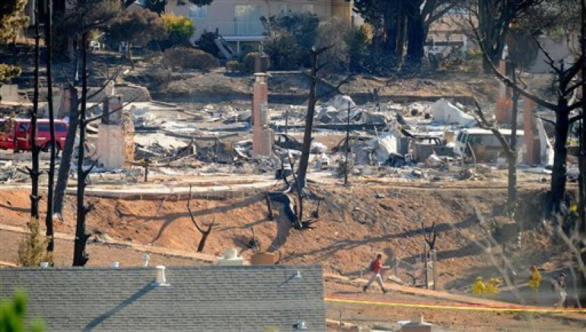 An emergency worker walks through an area of burned homes in San Bruno, Calif., on Saturday, Sept. 11, 2010. On Thursday, a gas line rupture caused a large explosion that killed at least four people and leveled dozens of homes. (AP Photo/Noah Berger)