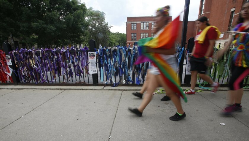 In this Sunday, June 28, 2015 photo, parade-goers walk by a decorated school fence on their way to Chicago's Gay Pride Parade. With the help of his family, students at the Nettelhorst School and other volunteers, Boy Scout David Fite decorated the street scene in rainbow colors. (AP Photo/Martha Ir