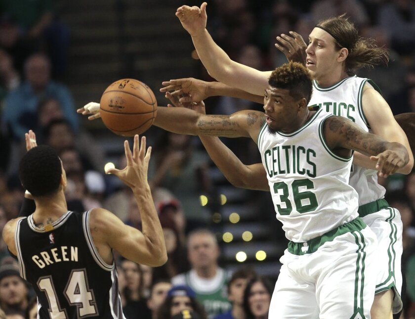 San Antonio Spurs guard Danny Green, left, vies for control of the ball with Boston Celtics guard Marcus Smart, center, and center Kelly Olynyk, right, in the second quarter of an NBA basketball game, Sunday, Nov. 1, 2015, in Boston. (AP Photo/Steven Senne)