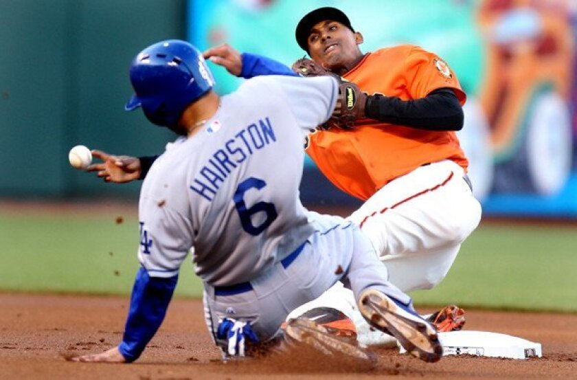 Giants second baseman Joaquin Arias tries to complete a double play as Dodgers first baseman Jerry Hairston Jr. slides into second base during their game Friday night in San Francisco.