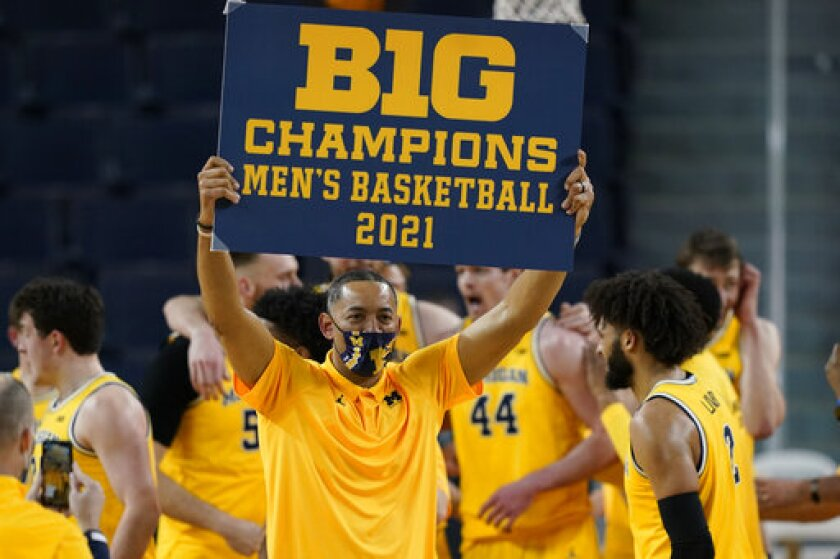 Michigan coach Juwan Howard holds a championship sign after the Wolverines clinched the Big Ten title last March.