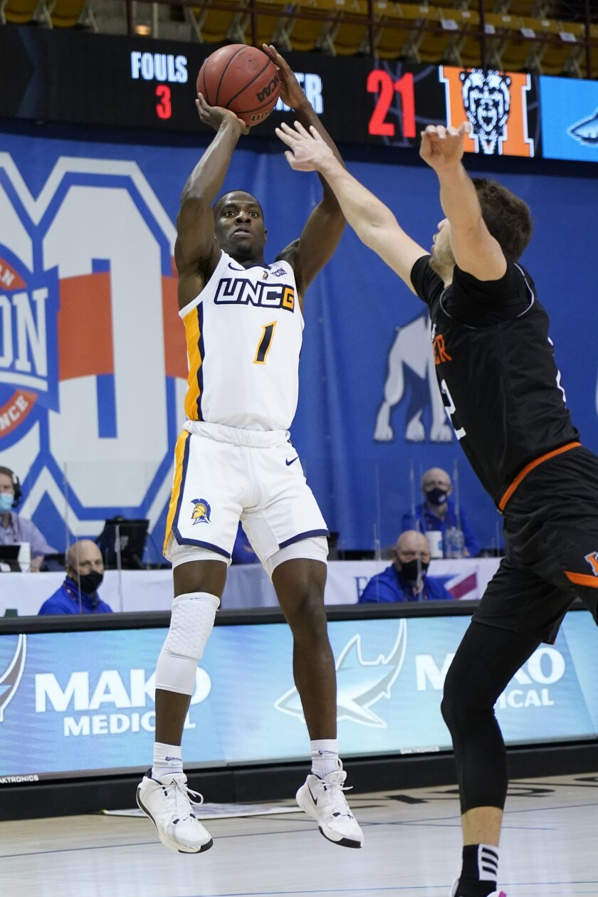 UNC-Greensboro guard Isaiah Miller (1) shoots for the basket over Mercer forward Felipe Haase (22) in the first half of an NCAA men's college basketball championship game for the Southern Conference tournament, Monday, March 8, 2021, in Asheville, N.C. (AP Photo/Kathy Kmonicek)