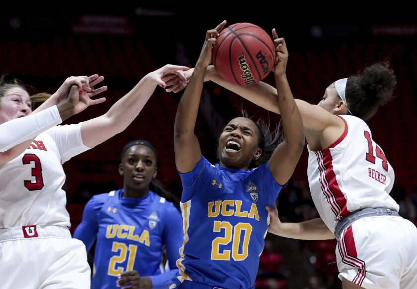UCLA's Charisma Osborne grabs a rebound in a crowd of players against Utah on Jan. 10, 2020.