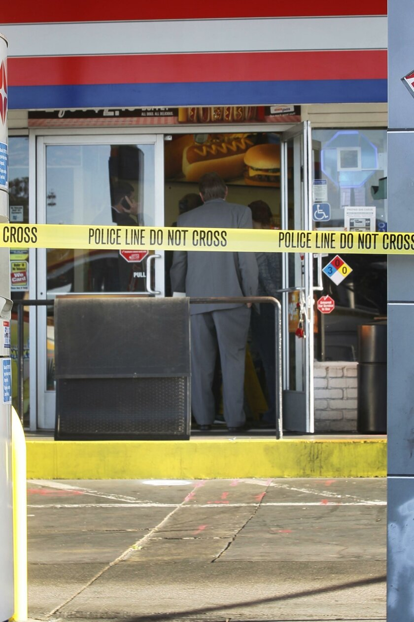 SDPD detectives gathered in the doorway of the gas station.