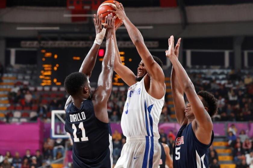 Alpha Diallo (i) y Ty-Shon Alexander (d) de Estados Unidos bloquean a Lionel Figueroa (c) de R.Dominicana este domingo en un juego de baloncesto entre República Dominicana y Estados Unidos en los Juegos Panamericanos Lima 2019, en Lima (Perú). EFE/Paolo Aguilar