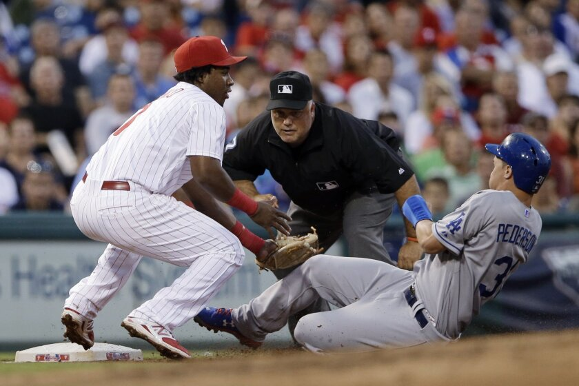 Philadelphia Phillies third baseman Maikel Franco, left, tags out Los Angeles Dodgers' Joc Pederson, right, after Pederson tried to advance to third base on a single by Alberto Callaspo during the fourth inning of a baseball game, Wednesday, Aug. 5, 2015, in Philadelphia. At center is umpire Brian