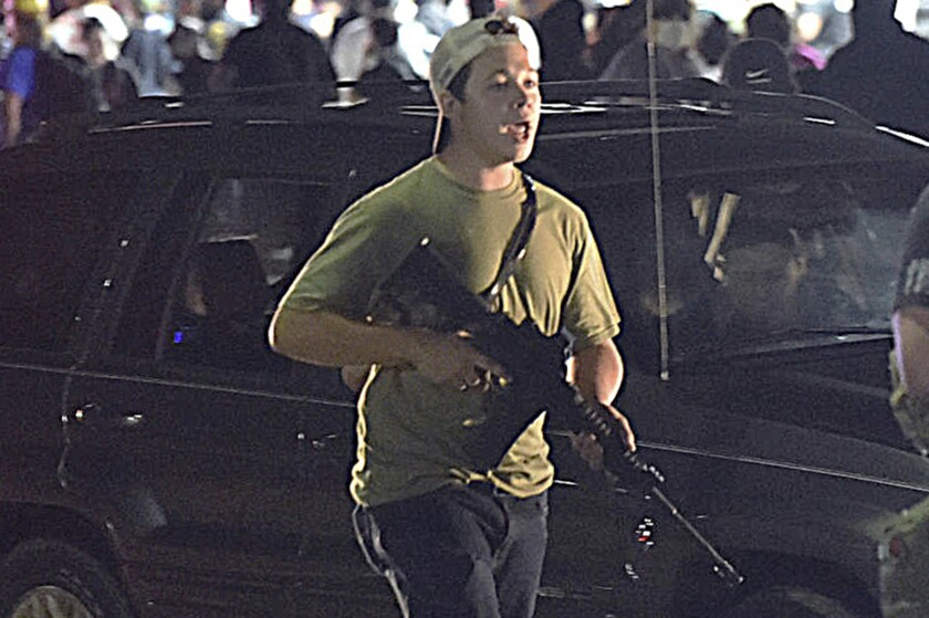 """FILE - In this Tuesday, Aug. 25, 2020, file photo, Kyle Rittenhouse carries a weapon as he walks along Sheridan Road in Kenosha, Wis., during a night of unrest following the weekend police shooting of Jacob Blake. In a document filed Thursday, Oct. 8, 2020, defense attorneys say sending Rittenhouse, accused of killing two protesters days after Jacob Blake was shot by police in Kenosha, Wis., to stand trial in Wisconsin would """"turn him over to the mob."""" (Adam Rogan/The Journal Times via AP, File)"""