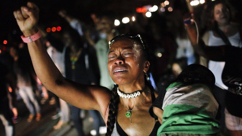 Protester Tammy Sum cries as she holds her son during a Black Lives Matter rally in Inglewood on July 10.