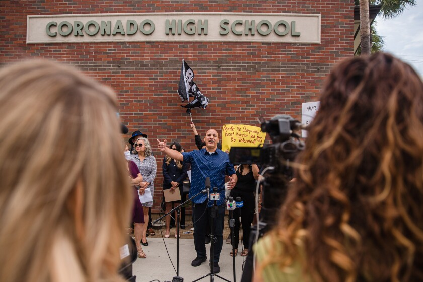 Andres Rivera, a father of an Orange Glen High School basketball player, speaks at a rally in front of Coronado High School