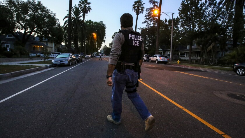 Jorge Field of ICE Enforcement and Removal Operations makes his way to an Aug. 12 raid in Riverside. On Monday, authorities said more than 240 people across Southern California were taken into federal custody last week after a four-day sweep for immigrants with criminal records in the country illegally.