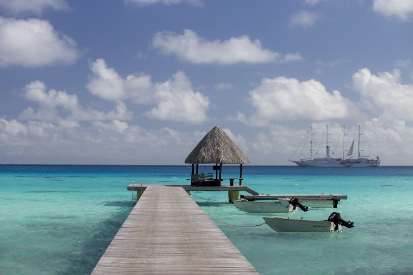 The private dock at Hotel Kia Ora Resort & Spa, French Polynesia. A ship from Windstar Cruises is seen in the distance.