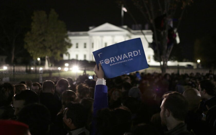 """A Democratic supporter holds a """"Forward"""" sign as people gather to celebrate President Obama's re-election in front of the White House in Washington."""