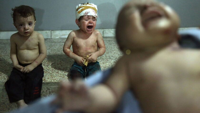 Injured Syrian children cry as they wait to receive treatment at a makeshift hospital in Jobar, Syri
