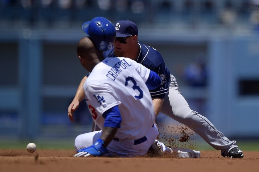 Los Angeles Dodgers' Carl Crawford, left, steals second as San Diego Padres second baseman Brooks Conrad takes a late throw from home during the first inning of a baseball game, Sunday, July 13, 2014, in Los Angeles. (AP Photo/Mark J. Terrill)