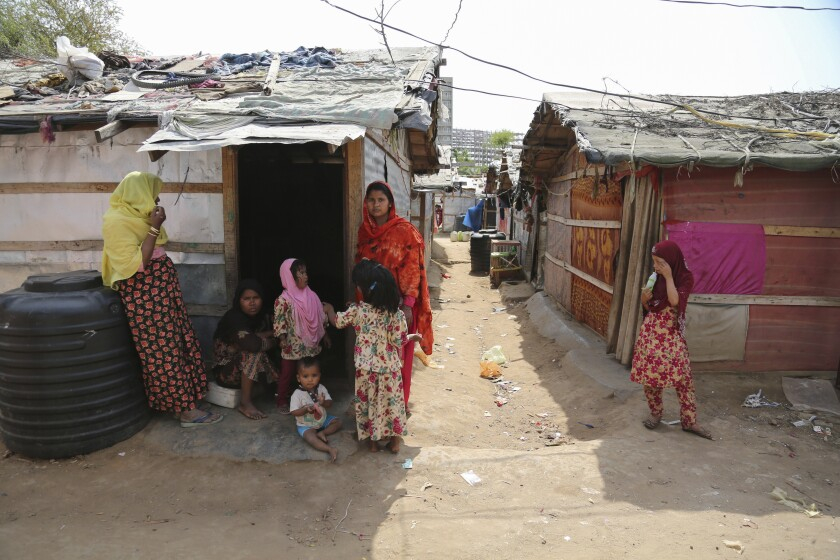 Rohingya refugees stand outside their makeshift camp on the outskirts of Jammu, India, Sunday, March 7, 2021. Authorities in Indian-controlled Kashmir have sent at least 168 Rohingya refugees to a holding center in a process which they say is to deport thousands of the refugees living in the region.(AP Photo/Channi Anand)