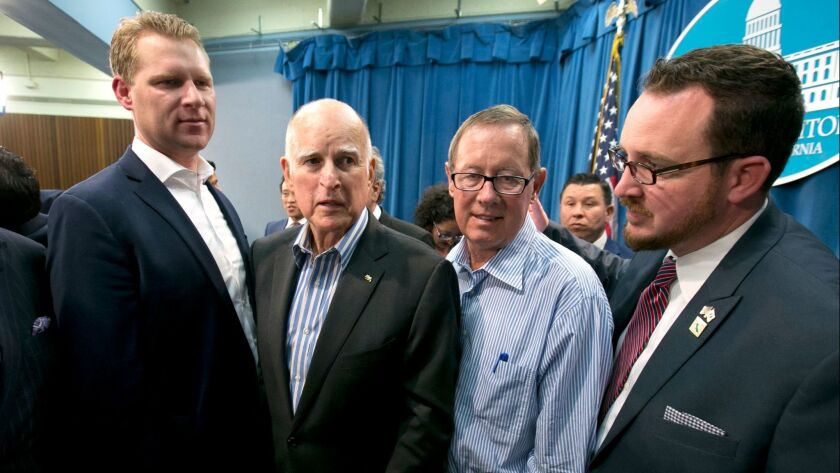 Gov. Jerry Brown, flanked by Republican legislators Chad Mayes, left, Tom Berryhill, second from right, and Devon Mathis, right, on July 17, after the Legislature approved an extension of cap and trade.