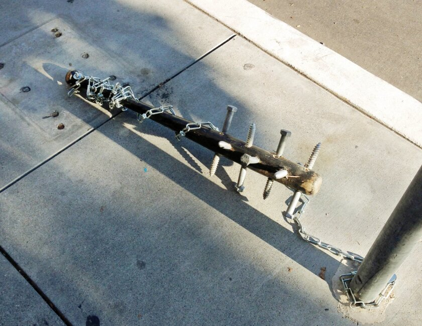 This Thursday, Nov. 26, 2015 photo provided by Pablo Diaz-Gutierrez shows a baseball bat with large lag screws embedded in it, chained to a pole in the Mission district San Francisco. Police are asking for help in finding who is chaining up these spiked bats to poles throughout the city. SFPD Sgt. Michael Andraychak says officers first received reports of spiked wooden or metal bats appearing on poles and parking meters in the city on Thanksgiving morning. At least 27 had been found by late Friday. (Pablo Diaz-Gutierrez via AP)
