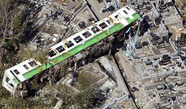 A train car washed away by the tsunami lies amid a graveyard in Onagawa.