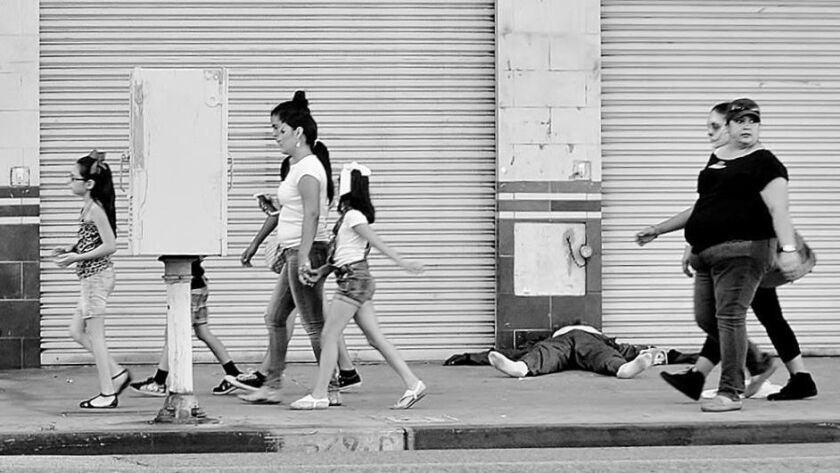 A family walks past a man passed out near the corner of 6th and Los Angeles streets in November of 2015.