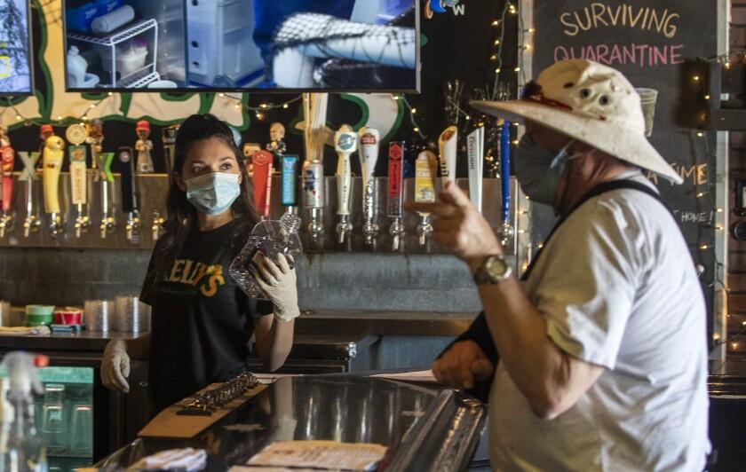 Bartender Brianna Van De Mortel takes a beer order from a customer at Kelly's Korner Tavern.