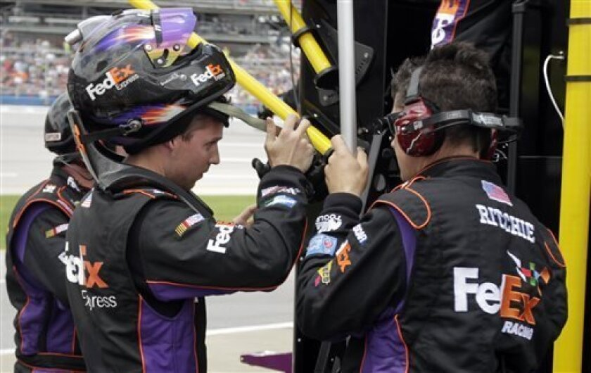 NASCAR Sprint Cup Series driver Denny Hamlin, left, talks with pit crew members after he was relieved by driver Brian Vickers on the first caution during the NASCAR Sprint Cup Series Aaron's 499 auto race at Talladega Superspeedway in Talladega, Ala., Sunday, May 5, 2013. (AP Photo/Jay Sailors)