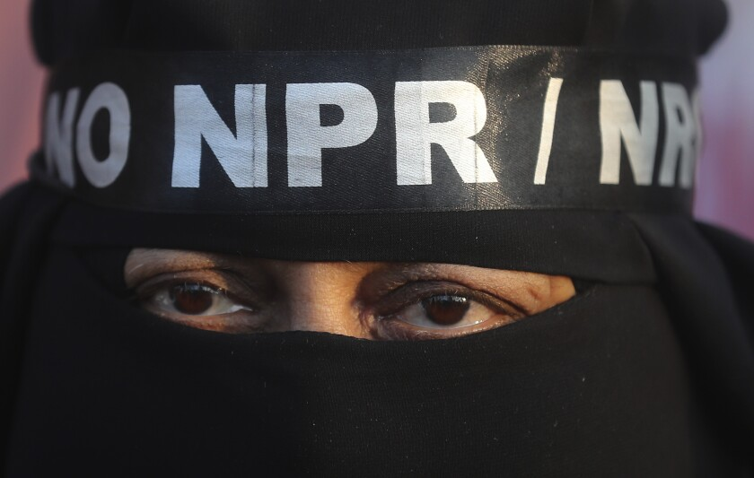 FILE- In this Jan. 24, 2020 file photo, an Indian Muslim wears a headband against a proposed nationwide citizens registry as she participates in a protest against a new citizenship law in Mumbai, India. India's ruling Hindu nationalist-led government said Tuesday it was still weighing whether to roll out a nationwide citizenship registry, an exercise it says would weed out illegal foreign nationals, amid ongoing protests against a citizenship law that fast-tracks naturalization for some religious minorities from three neighboring countries but not Muslims (AP Photo/Rafiq Maqbool)
