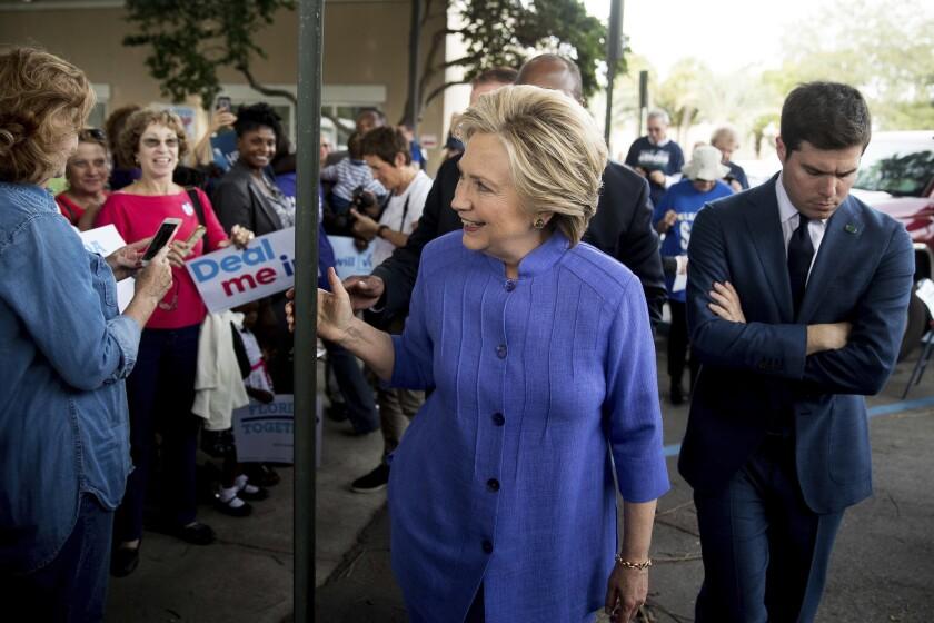 Hillary Clinton saluda a partidarios durante una parada en Pompano Beach, Florida, el 30 de octubre del 2016. La acompaña pensativo su secretario de prensa Nick Merrill. Clinton reanudó su campaña con bríos tras el anuncio del FBI de que reabría una investigación del uso de un servidor privado para enviar correos electrónicos siendo secretaria de Estado, confiada en que eso puede ayudarla a movilizar a votantes que podían sentirse poco motivados para acudir a las urnas a la luz de la ventaja que le ha sacado a Donald Trump en las encuestas. (AP Photo/Andrew Harnik)