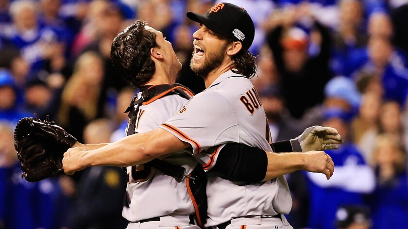 San Francisco Giants catcher Buster Posey, left, celebrates with pitcher Madison Bumgarner following a 3-2 victory over the Kansas City Royals in Game 7 of the World Series.
