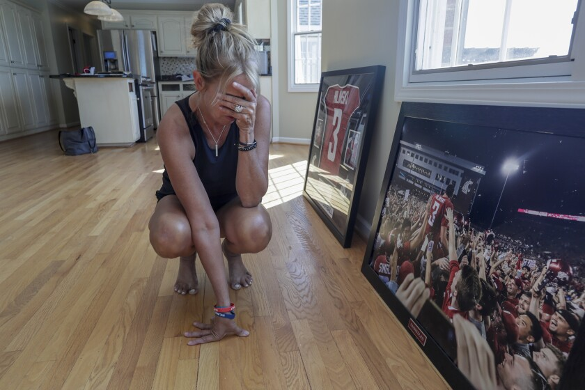 Kym Hilinski pauses as she looks at a photo of her son, Tyler, after he led Washington State to a comeback victory over Boise State in 2017.