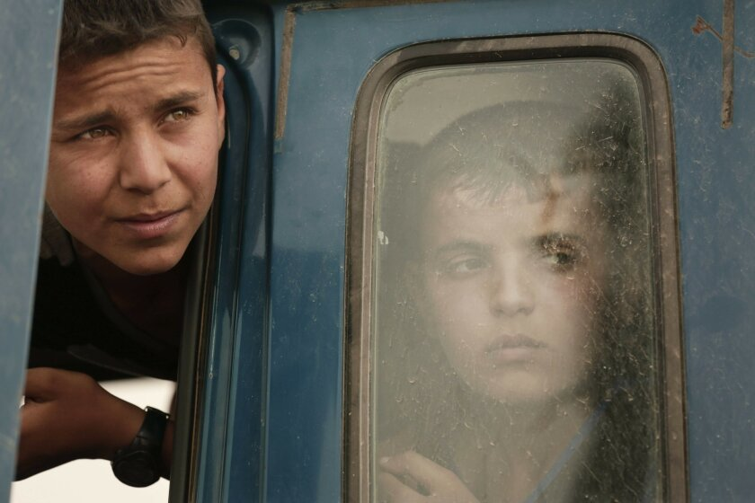 FILE - In this Sunday, March 20, 2016 photo, two boys in a truck in a convoy of families fleeing Islamic State-held Hit, Iraq, wait at a checkpoint on the western edge of Ramadi, Iraq. Iraq's government is setting its sight on Mosul, Iraq's second largest city that has been under IS control since J