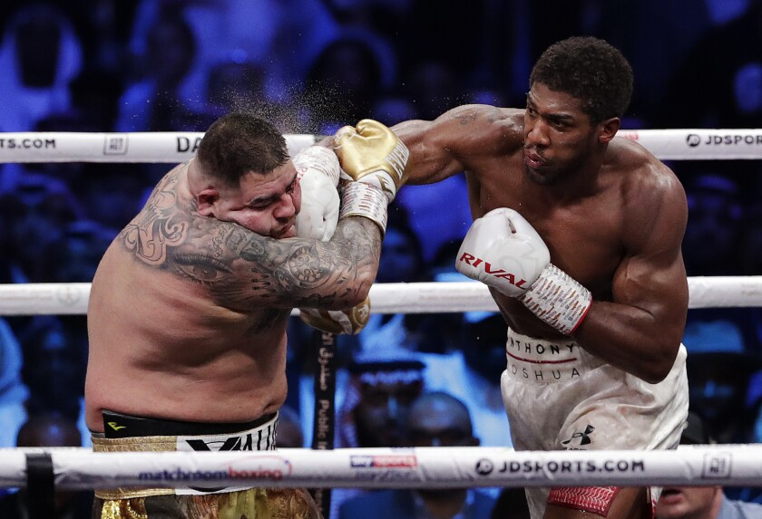 FILE - Defending champion Andy Ruiz Jr., left, takes a right cross to the face during his fight against Britain's Anthony Joshua in their World Heavyweight Championship contest at the Diriyah Arena, Riyadh, Saudi Arabia, in this Dec. 8, 2019, file photo. Andy Ruiz Jr. has heard all the fat jokes, and understands he has a reputation to rehabilitate. The former heavyweight champion also knows his comeback fight against 40-year-old Chris Arreola has been criticized both for the quality of opponent and the price fans will have to pay to watch it. (AP Photo/Hassan Ammar, File)