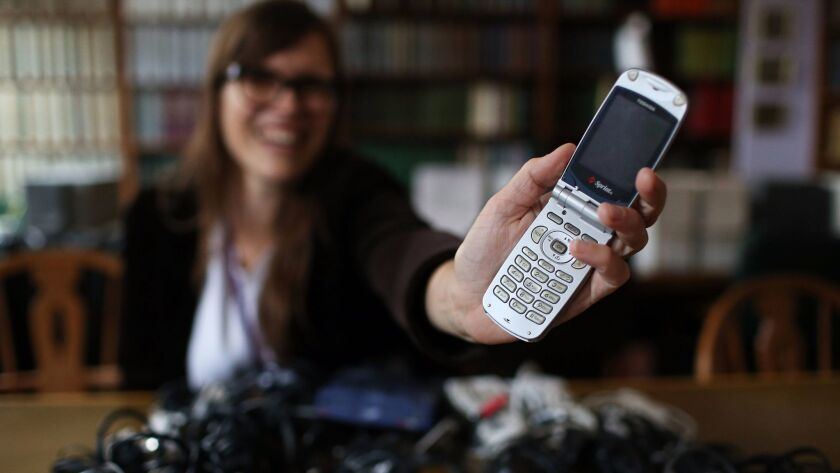 A woman holds a flip-phone model from the early 2000s in Evanston, Ill. on Oct. 24, 2015.