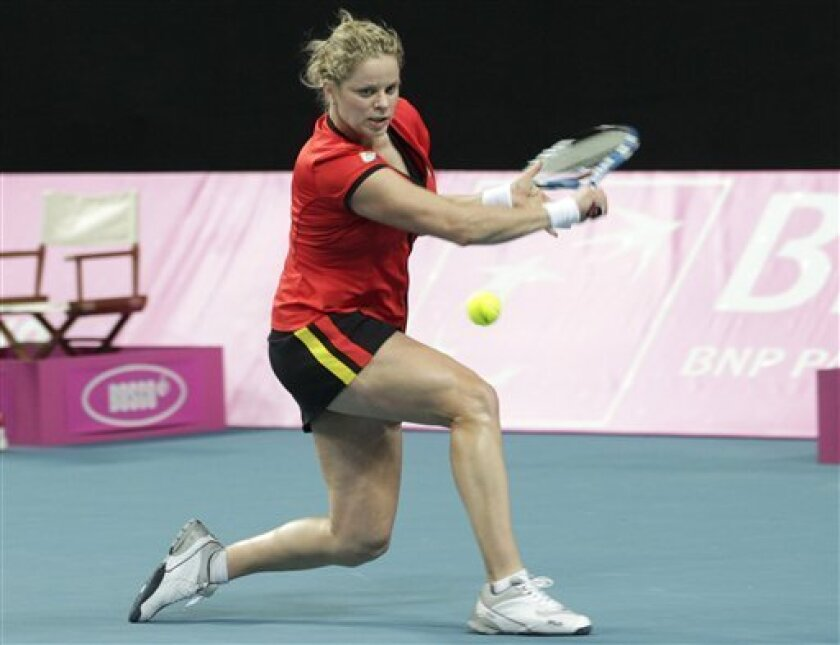 Belgium's Kim Clijsters returns the ball to US player Melanie Oudin during the World Group Fed Cup match in Antwerp, Belgium, Saturday, Feb. 5, 2011. Belgium leads on the first day 2-0. (AP Photo/Yves Logghe)