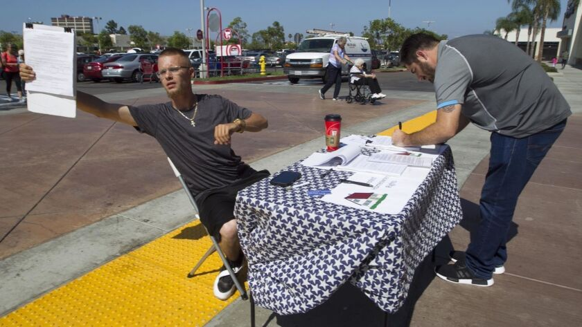 Something that won't be seen for a while: gathering ballot petition signatures at a shopping center. In this 2018 file photo, William Collins beckons people exiting the Target store in Clairemont to sign a petition on vacation rentals as Jon McKinney from Chollas View is doing.