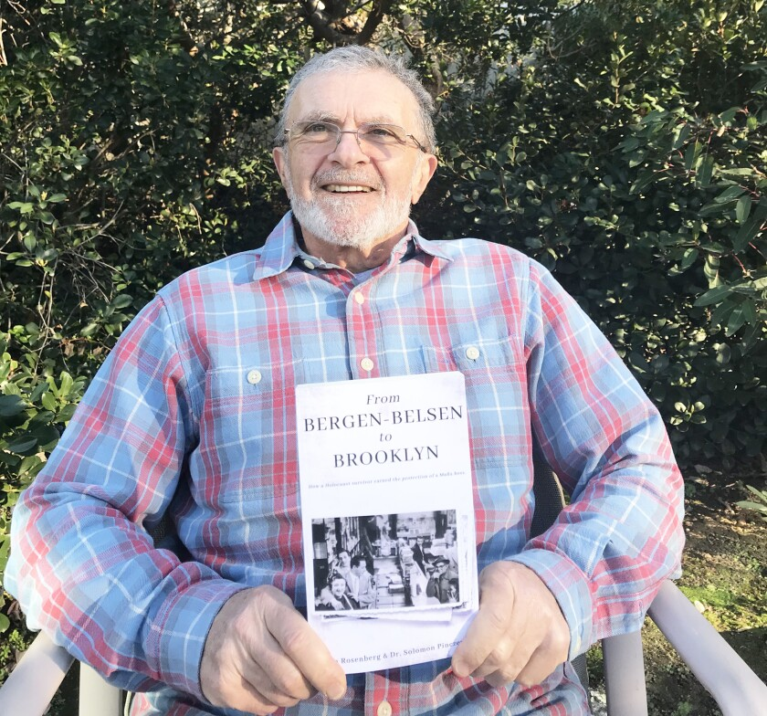 Sol Pinczewski holding the book detailing his family's history.
