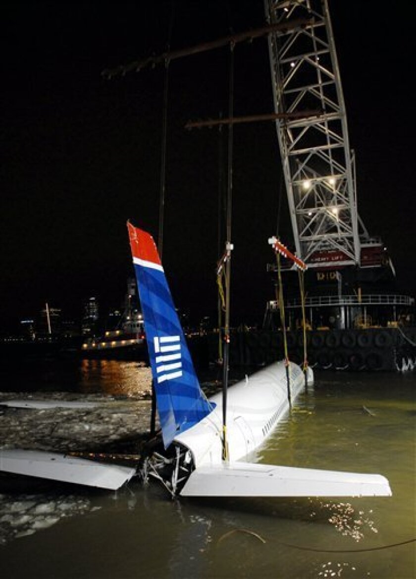 """A heavy lift crane removes US Airways flight 1549 from its makeshift mooring along a seawall in lower Manhattan, Saturday, Jan. 17, 2009 in New York.  Investigators began interviewing the pilot, Chesley B. """"Sully"""" Sullenberger, and his co-pilot for the first time Saturday. Sullenberger guided the c"""