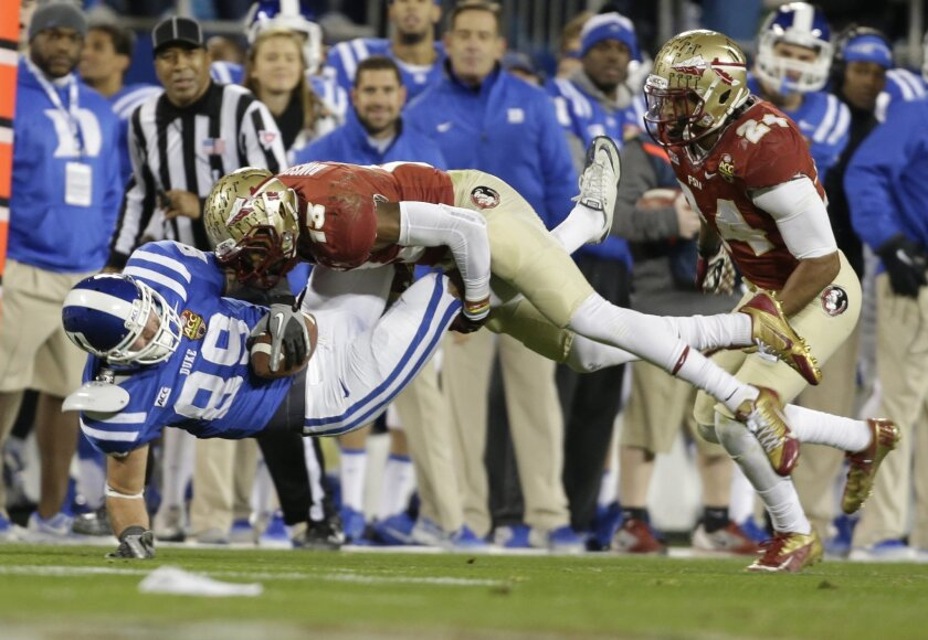 FILE - In this Saturday, Dec. 7, 2013, file photo, Duke's Braxton Deaver (89) is hit by Florida State's Jalen Ramsey (13) in the first half of the Atlantic Coast Conference Championship NCAA football game in Charlotte, N.C. Either the Tennessee Titans or Cleveland Browns could wind up with No. 1 pi