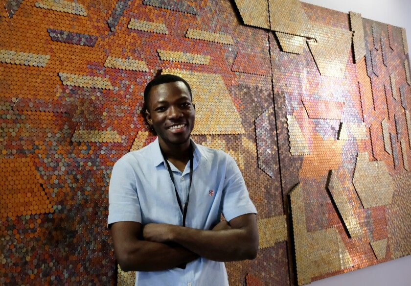 Yaw Owusu, a Ghanaian artist, stands in front of his work at ArtX Lagos in November 2017.