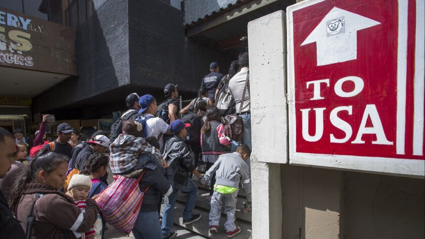 Migrants wait to ask for asylum in the U.S.
