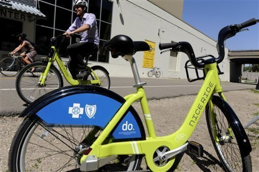 In a photo made Wednesday, May 19, 2010 in Minneapolis, Jake Quarstad cycles along the Midtown Greenway as he demonstrated two of the bikes that will be made available as part of a bike share program. (AP Photo/Jim Mone)
