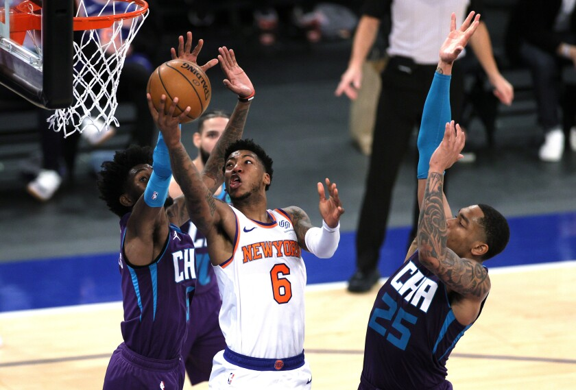 New York Knicks' Elfrid Payton goes to the basket as Charlotte Hornets' Jalen McDaniels, left, and P.J. Washington defend during the second half of an NBA basketball game Tuesday, April 20, 2021, in New York. (Sarah Stier/Pool Photo via AP)